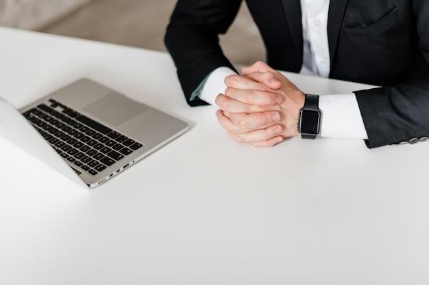 Mannelijke handen op werkplek met laptop