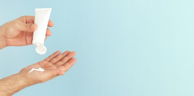 Mannelijke handen passen cosmetische huidverzorging vochtinbrengende crème of zalf toe op blauwe achtergrond
