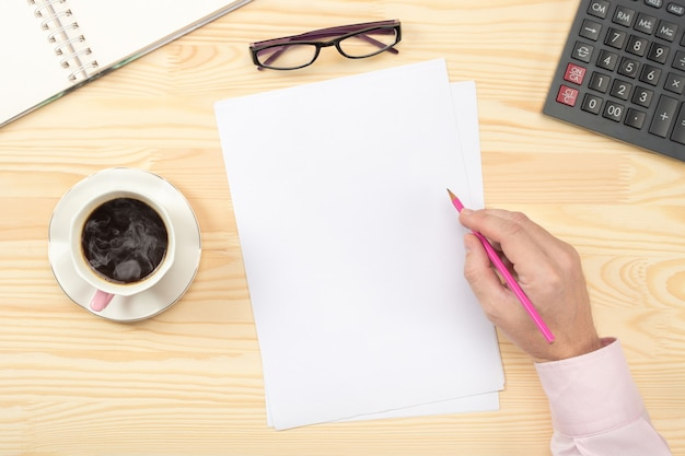 Mannelijke handen schrijven op lege blanco papier over houten tafel. zakenman die met documenten werkt. plat leggen