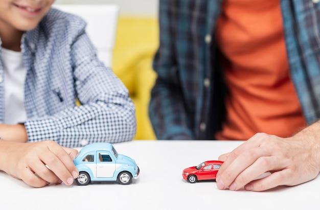 Mannelijke handen spelen met speelgoedauto's