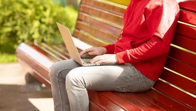 Mannelijke handen typen op laptop in het park