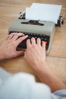 Mannelijke handen typen op oude typemachine op houten tafel