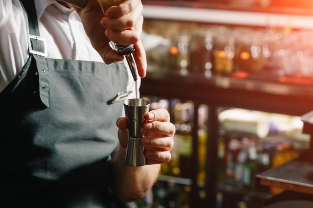 Mannelijke handen van de barman, maakt een cocktail op de bar, glazen met ijs.