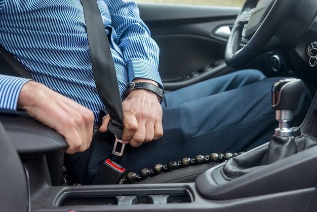 Mannelijke handen vergrendelen veiligheidsgordel, close-up