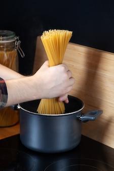 Mannelijke handen zetten een bos pasta in de kookpan,
