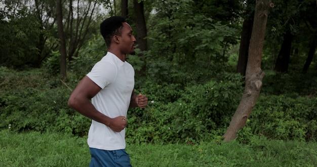 Mannelijke hardloper die 's ochtends cardiotraining op stadspark doet. afrikaanse man die buiten loopt. tracking shot runner trainen in de zomer. concept van gezonde levensstijl.