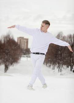 Mannelijke hiphopkunstenaar stellende buitenkant met sneeuw