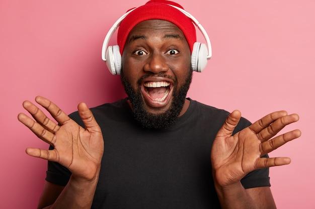 Mannelijke hipster luistert naar muziek in draadloze hoofdtelefoons geïsoleerd