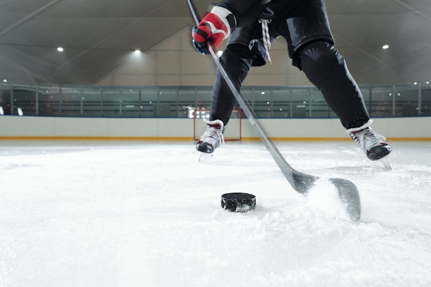 Mannelijke hockeyspeler in sportuniform, handschoenen en schaatsen die voor de camera naar beneden bewegen tegen de stadionomgeving terwijl hij puck gaat schieten