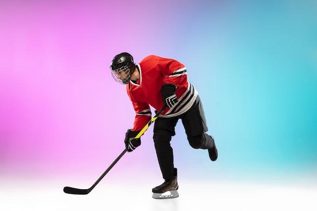 Mannelijke hockeyspeler met de stok op ijsbaan en neon gekleurde gradiëntachtergrond