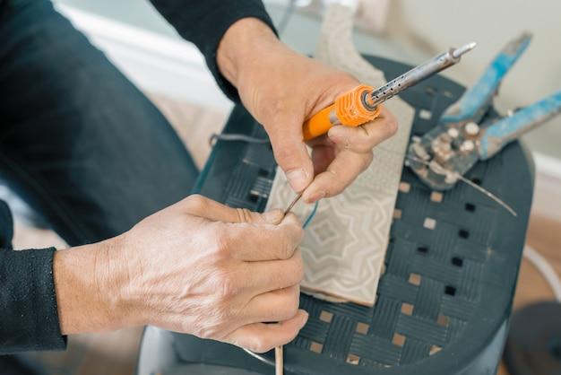 Mannelijke holding soldeerbout tool repareren