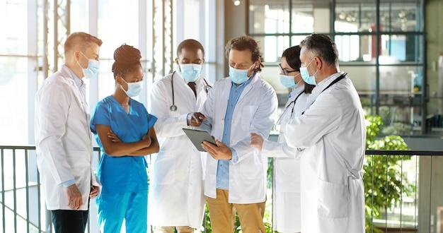 Mannelijke hoofd van de kliniek permanent met team van gemengde rassen artsen collega's en met behulp van tablet tijdens het kijken op het scherm. groep multi-etnische medici, mannen en vrouwen praten en discussiëren.