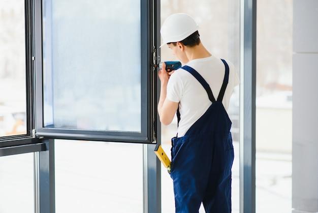Mannelijke industriële bouwersarbeider bij raaminstallatie bij het bouwen van bouwplaats