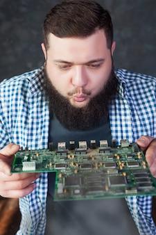 Mannelijke ingenieur blaast het stof van het moederbord