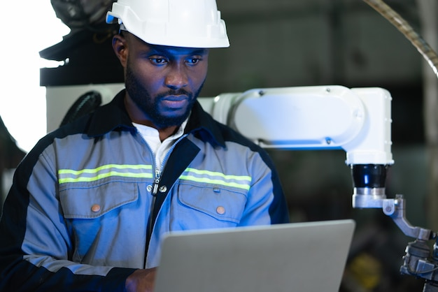 Mannelijke ingenieur controle en inspectie controle robotarm lasmachine met laptop in de fabriek