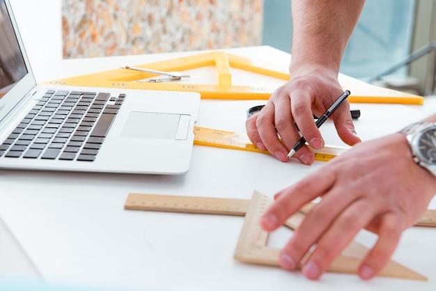 Mannelijke ingenieur die aan tekeningen en blauwdrukken werkt