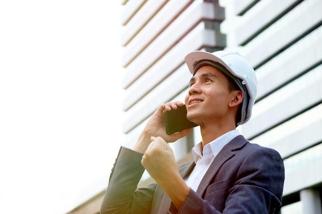 Mannelijke ingenieur die witte veiligheidshelm draagt die mobilofoonzonsopgang als achtergrond bij de bouw gebruikt.