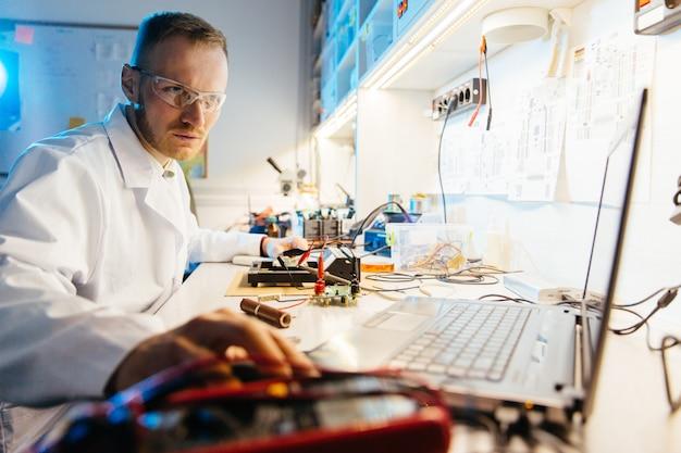 Mannelijke ingenieur in witte mantel die laptop voor het werk in elektronisch laboratorium met behulp van