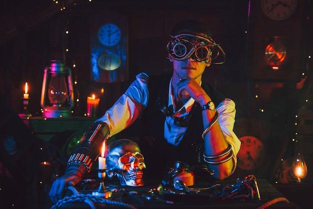 Mannelijke ingenieur met een cyberpunkbril en een steampunkkostuum in een werkplaats met neonlicht