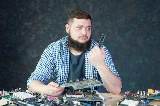 Mannelijke ingenieur werkt met kapotte computeronderdelen. elektronische apparaten die technologie herstellen