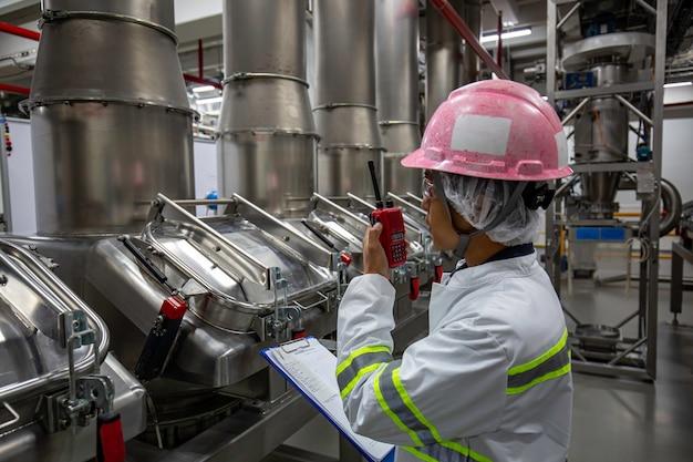 Mannelijke ingenieurs geluidsbescherming en uniform personeel. hand met draagbare radio-ontvanger voor communicatie werkinspectie proces poederkelder in de fabriek met verticale roestvrijstalen tanks