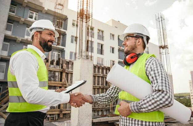 Mannelijke inspecteur handen schudden en vergadering op bouwplaats