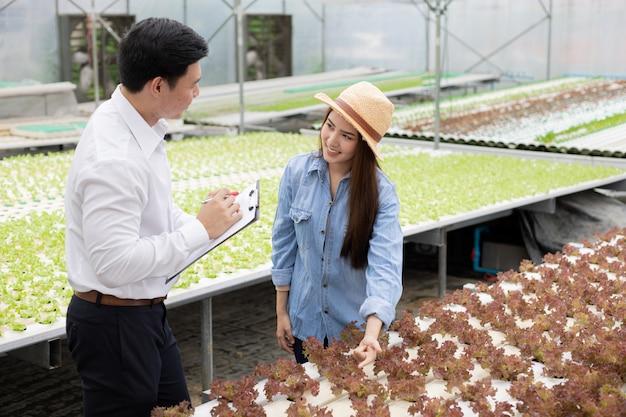 Mannelijke inspecteurs inspecteren en registreren de kwaliteit van biologische groenten met vrouwelijke boeren die begeleiding bieden.