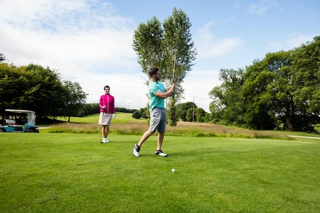 Mannelijke instructeur bijwonende vrouw in het leren van golf