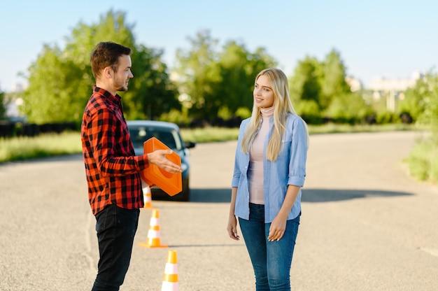 Mannelijke instructeur met verkeerskegel en student op weg, les in rijschool. man die dame leert voertuig te besturen. rijbewijs opleiding