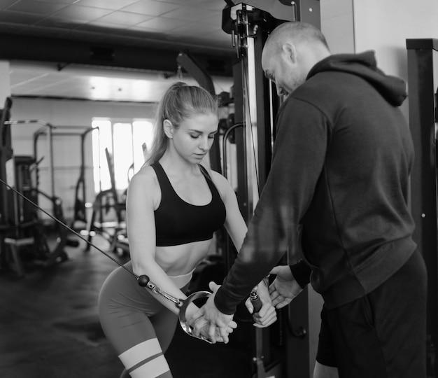 Mannelijke instructeur traint blonde vrouw doen oefening in cross-overs in crossover machine op sportschool