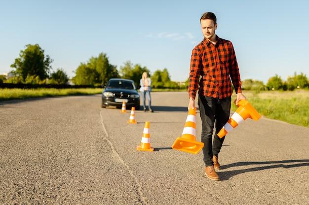 Mannelijke instructeur zet verkeerskegels op de weg, rijschool. man die dame leert voertuig te besturen. rijbewijs opleiding