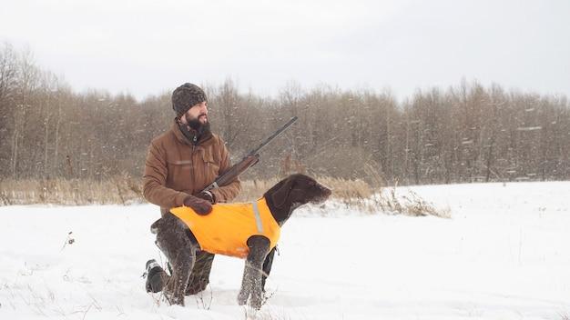 Mannelijke jager en zijn hond wachten op hun prooi in een veld, zijaanzicht