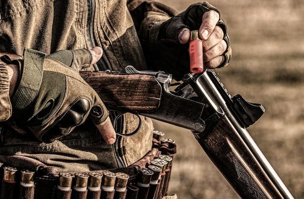 Mannelijke jager klaar om te jagen. detailopname. jager man. jachtperiode. mannetje met een pistool, geweer.