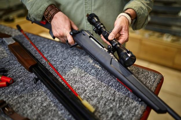 Mannelijke jager met laadstok reinigt geweer in wapenwinkel. wapenwinkelinterieur, munitie- en munitie-assortiment, vuurwapenkeuze, schiethobby en lifestyle