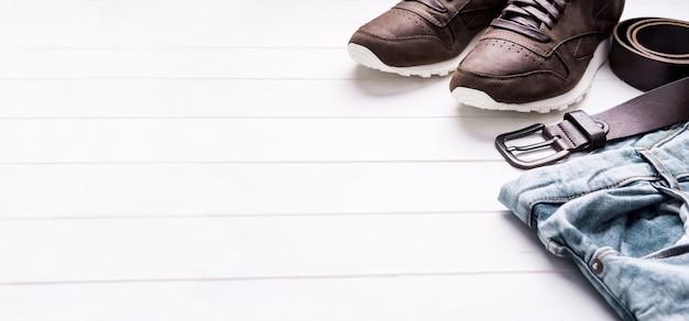 Mannelijke jeansriem en schoenen op houten achtergrond met tekstruimte met copyspace