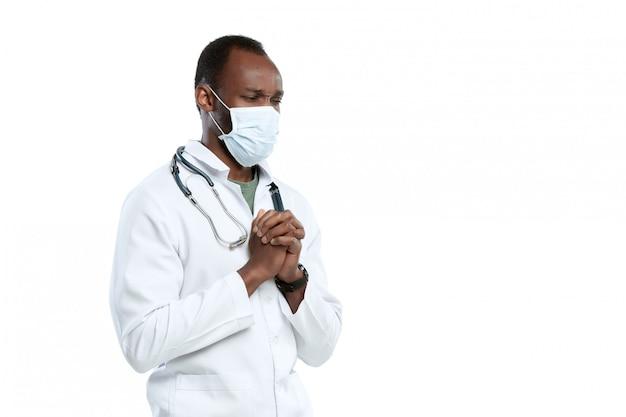 Mannelijke jonge arts met stethoscoop en gezichtsmasker dat op wit wordt geïsoleerd