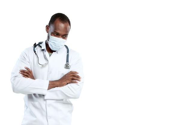 Mannelijke jonge arts met stethoscoop en gezichtsmasker dat op witte muur wordt geïsoleerd