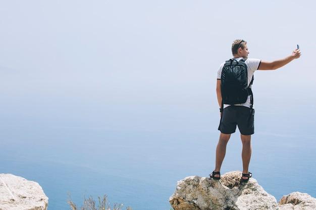 Mannelijke jonge volwassene met een mobiele telefoon in een landschap met de zee