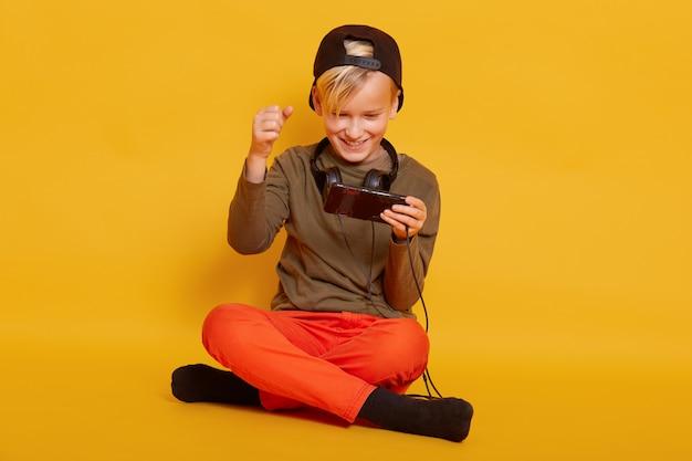 Mannelijke jongen spelen van spel op mobiele telefoon zittend op de vloer in geïsoleerd op geel, het spelen van zijn favoriete online spel via de telefoon, benen gekruist houdt, vuisten gebald.