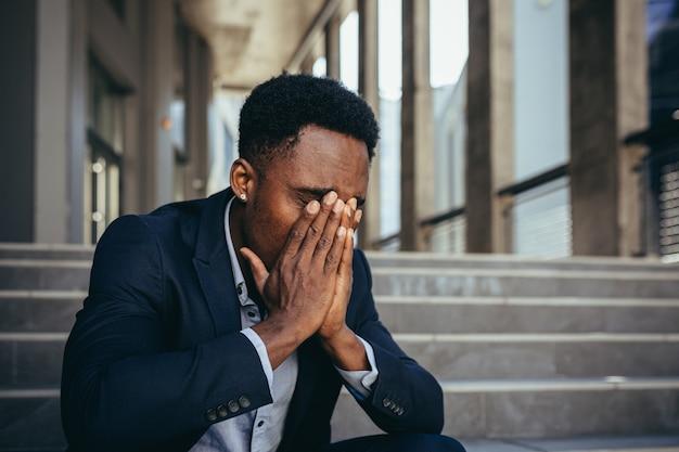 Mannelijke kantoormedewerker moe na het werk, afro-amerikaan heeft ernstige hoofdpijn, zittend op een trap in de buurt van kantoor