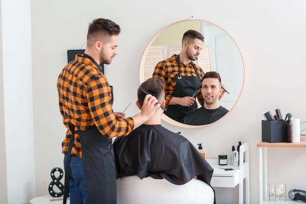 Mannelijke kapper die met cliënt in salon werkt