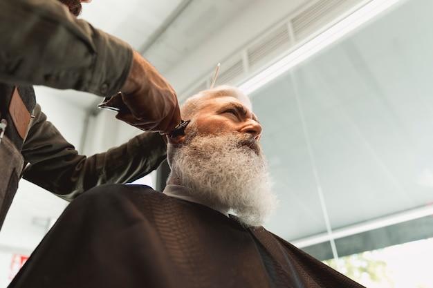 Mannelijke kapper die met haar van de hogere mens in herenkapper werkt