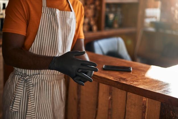 Mannelijke kapper die zwarte steriele handschoenen op handen zet