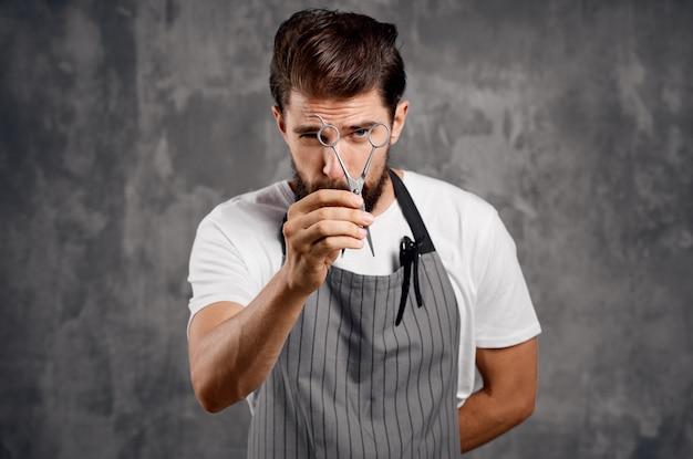 Mannelijke kapper in een schort met een kam in zijn handen en een schaar