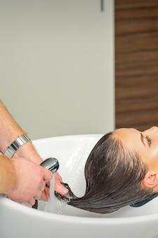 Mannelijke kapper spoelt haar van jonge vrouw in kapsalon
