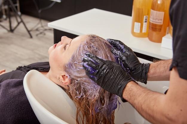 Mannelijke kapper toning klant haar in salon