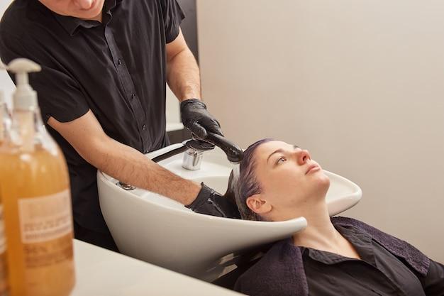 Mannelijke kapper wast toning shampoo uit het haar van de klant