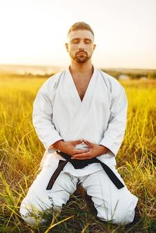Mannelijke karate vechter zittend op de grond in zomer veld. vechtsport training buiten