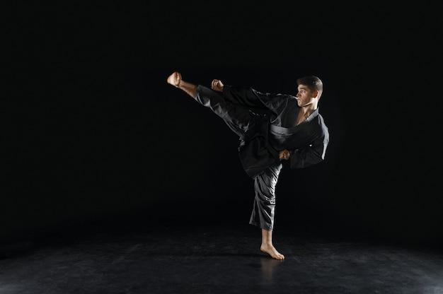 Mannelijke karateka, vechter in zwarte kimono, gevechtshouding. man op training, vechtsporten, training voordat de concurrentie wordt bestreden