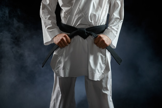 Mannelijke karateka, vechter met zwarte band, gevechtshouding. man op karatetraining, vechtsporten, training voordat de concurrentie wordt bestreden